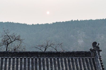 LUOYANG, CHINA - MARCH 20, 2017: sun over roof of temple on East Hill of Chinese Buddhist monument Longmen Grottoes in spring. The complex was inscribed upon the UNESCO World Heritage List in 2000