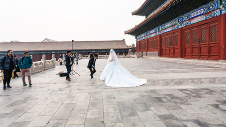 BEIJING, CHINA - MARCH 19, 2017: photographer and bride in photosession at courtyard of Imperial Ancestral Temple (Taimiao, Working Peoples Cultural Palace) in Beijing Imperial city in spring.