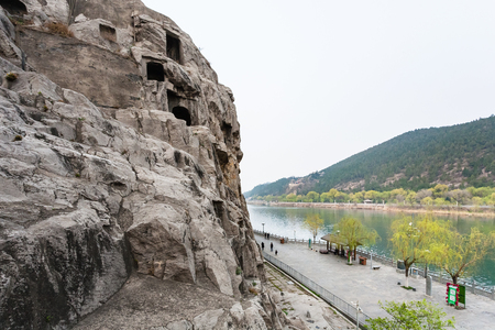 LUOYANG, CHINA - MARCH 20, 2017: above view of waterfront with tourists in Chinese Buddhist monument Longmen Grottoes. The complex was inscribed upon the UNESCO World Heritage List in 2000