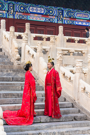 BEIJING, CHINA - MARCH 19, 2017: couple in traditional dresses on steps of Hall for Worship of Ancestors in Imperial Ancestral Temple (Taimiao) in Beijing Imperial city in spring.
