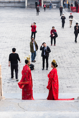 BEIJING, CHINA - MARCH 19, 2017: couple in traditional dresses and photographer on courtyard of Imperial Ancestral Temple (Taimiao, Working Peoples Cultural Palace) in Beijing Imperial city in spring