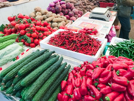 YANGSHUO, CHINA - MARCH 28, 2017: fresh vegetables near counter on market in Yangshuo city. The town is resort destination for domestic and foreign tourists because of scenic karst peaks