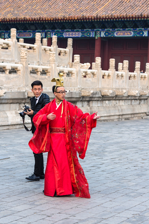 BEIJING, CHINA - MARCH 19, 2017: man in traditional costume and photographer on court of Imperial Ancestral Temple (Taimiao, Working Peoples Cultural Palace) in Beijing Imperial city in spring.