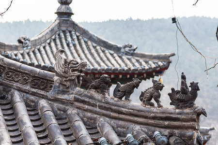 gloaming: LUOYANG, CHINA - MARCH 20, 2017: roof decoration of temple on East Hill of Chinese Buddhist monument Longmen Grottoes in spring. The complex was inscribed upon the UNESCO World Heritage List in 2000 Editorial