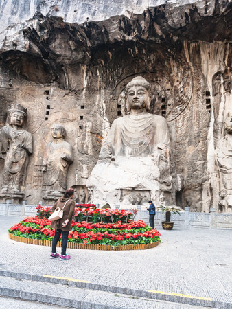 LUOYANG, CHINA - MARCH 20, 2017: people near carved The Big Vairocana statue in main Longmen Grotto (Longmen Caves). The complex was inscribed upon the UNESCO World Heritage List in 2000 Editorial