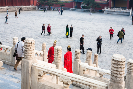BEIJING, CHINA - MARCH 19, 2017: couple in red dresses and people on courtyard of Imperial Ancestral Temple (Taimiao, Working Peoples Cultural Palace) in Beijing Imperial city in spring Editorial