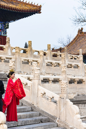 BEIJING, CHINA - MARCH 19, 2017: woman in traditional costume and photographer on court of Imperial Ancestral Temple (Taimiao, Working Peoples Cultural Palace) in Beijing Imperial city in spring.