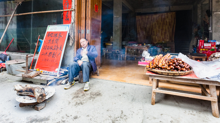 local 27: CHENGYANG, CHINA - MARCH 27, 2017: seller near local eatery and smokehouse in Chengyang village of Sanjiang Dong Autonomous County in spring. Chengyang includes eight villages of the Dong people