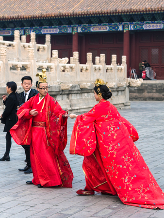 BEIJING, CHINA - MARCH 19, 2017: couple in traditional dresses and photographer on court of Imperial Ancestral Temple (Taimiao, Working Peoples Cultural Palace) in Beijing Imperial city in spring.