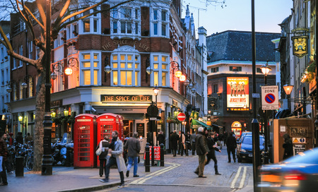 LONDON, UK - JANUARY 20, 2009: view of people, bars, restaurants on crossing Moor st and Romilly st from Charing Cross Road of Soho district of City of Westminster in London winter evening.