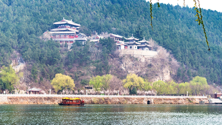 he: travel to China - view of memorial on East Hill of Chinese Buddhist monument Longmen Grottoes (Dragons Gate Grottoes, Longmen Caves) through Yi river in spring season
