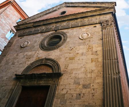 travel to Italy - facade of Church Saint Maria of Snows (Santa Maria delle Nevi) on Via Banchi di Sopra in Siena city in winter Фото со стока