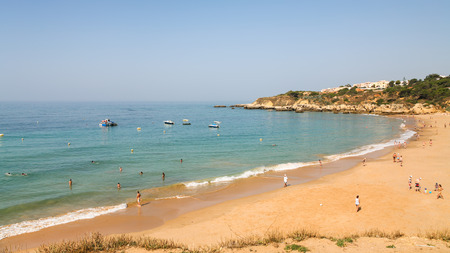 Travel to Algarve Portugal - people on urban beach Praia dos Alemaes in Albufeira city