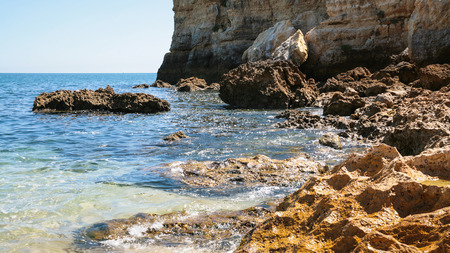 Travel to Algarve Portugal - coquina rocks on coastline of beach Praia Maria Luisa near Albufeira city in sunny day