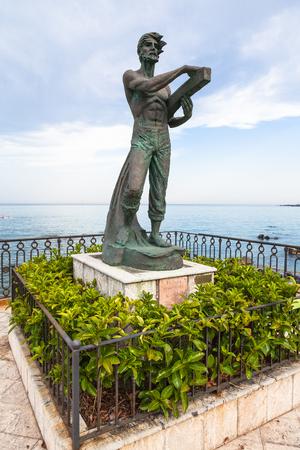 GIARDINI NAXOS, ITALY - JUNE 28, 2017: sculpture L Uomo e il Mare (Man and the Sea) on waterfront in Giardini-Naxos town. Giardini Naxos is seaside resort on Ionian Sea coast since the 1970s