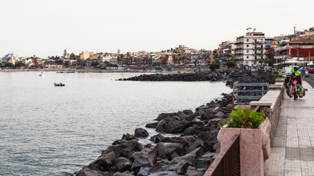 GIARDINI NAXOS, ITALY - JUNE 28, 2017: people on waterfront in Giardini-Naxos town in summer evening. Giardini Naxos is seaside resort on Ionian Sea coast since the 1970s Editorial