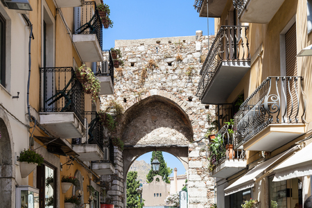 TAORMINA, ITALY - JUNE 29, 2017: medieval arch of old gateway Porta Catania in Taormina city. Taormina is resort town on Ionian Sea in Sicily