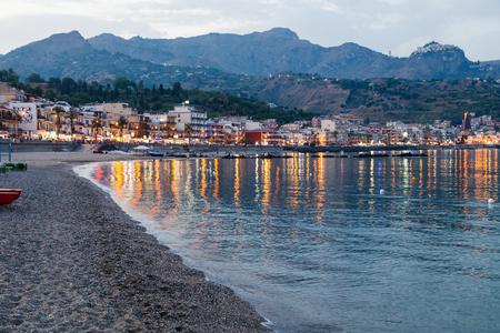 ionian: GIARDINI NAXOS, ITALY - JUNE 28, 2017: people on beach in Giardini-Naxos town view of Taormina city on cape in summer evening. Giardini Naxos is seaside resort on Ionian Sea coast since the 1970s Editorial