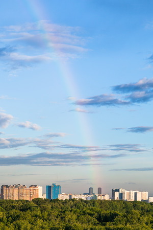 rainbow in blue evening sky over apartment houses and Timiryazevsky park in Moscow city in summer