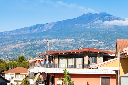 travel to Sicily, Italy - residential houses on street via ischia in Giardini Naxos town and view of Etna Mount in summer