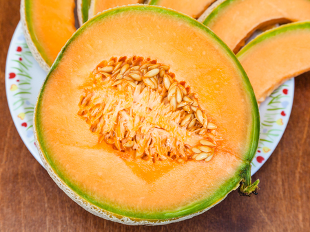 half of ripe sicilian muskmelon (cantaloupe melon) close up on plateon wooden table Stock Photo