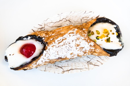 sprinkled: above view of typical sicilian pastry Cannoli sprinkled with confectioners sugar omn white plate