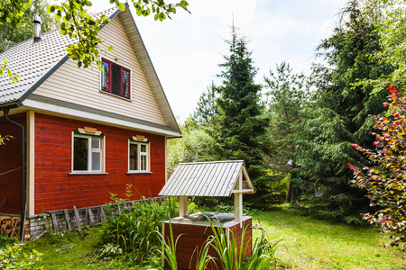 view of simple cottage and well from backyard in russian village in sunny summer day Stock Photo