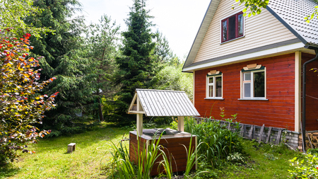 view of modern simple cottage and well from backyard in russian country in sunny summer day Stock Photo