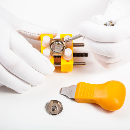 watchmaker workshop - cleaning battery place in quartz watch by screwdriver on white background