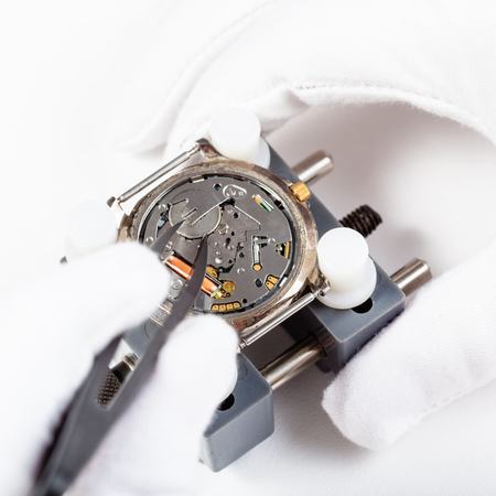 watchmaker workshop - replacing battery in quartz wristwatch close up by tweezers on white background Stock Photo