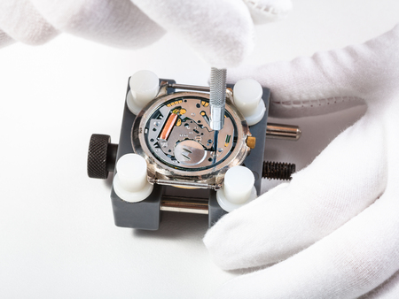 watchmaker workshop - repairing quartz watch close up with screwdriver on white background Stock Photo