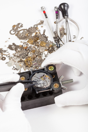 watchmaker workshop - repair of mechanic watch with spare parts by tweezers on white background