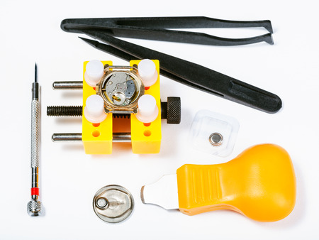 watchmaker workshop - top view of set of tools for replacing battery in watch on white background