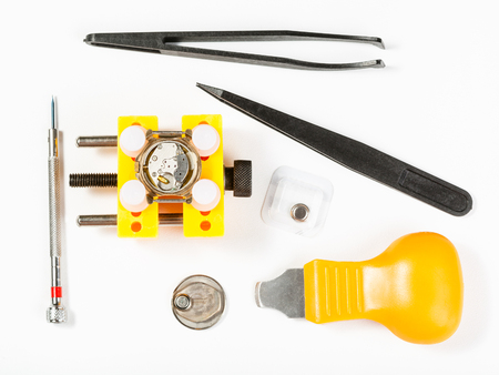watchmaker workshop - top view of kit for replacing battery in watch on white background
