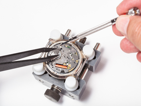 watchmaker workshop - replacement battery in quartz watch close up on white background
