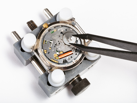 watchmaker workshop - replacement battery in quartz watch with tweezers close up on white background