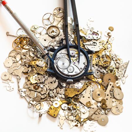 Uhrmacher-Workshop - Draufsicht Schraubenzieher, Pinzette über offene mechanische Uhr auf Haufen Uhr Ersatzteile auf weißem Hintergrund Standard-Bild - 83864365