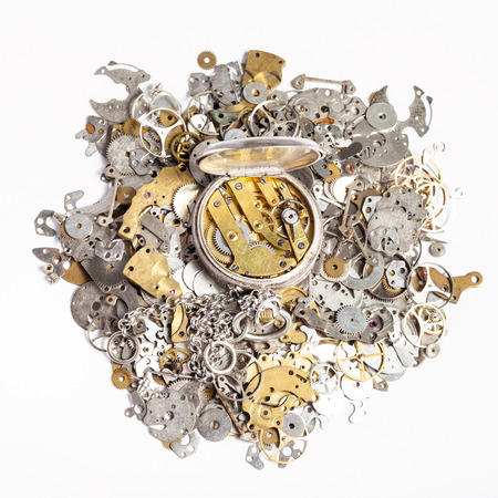 watchmaker workshop - top view of open silver pocket watch on heap of old clock spare parts on white background