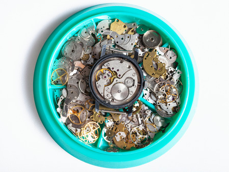watchmaker workshop - top view of disassembled watch in plate with clock spare parts on white background