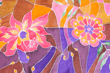 textile background - hand painted floral ornament on silk batik scarf