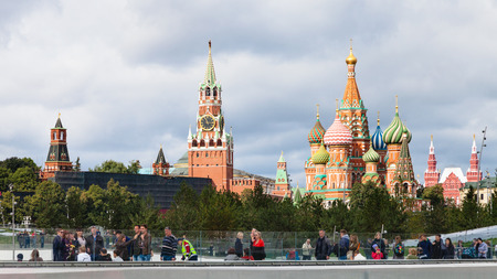 MOSCOW, RUSSIA - SEPTEMBER 16, 2017: tourists walk on floating bridge of Zaryadye park and view of Kremlin Tower and Cathedral in Moscow city. The park was inaugurated on 9 September 2017 Editorial