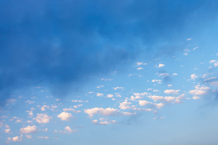 many little white clouds and rainy gray cloud in blue sky over Crimean Southern Coast in september evening