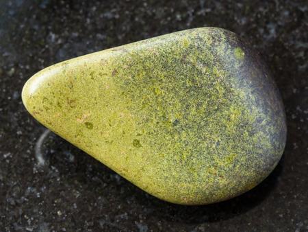 macro shooting of natural mineral rock specimen - tumbled epidote gemstone on dark granite background from Segozero, Karelia in Russia
