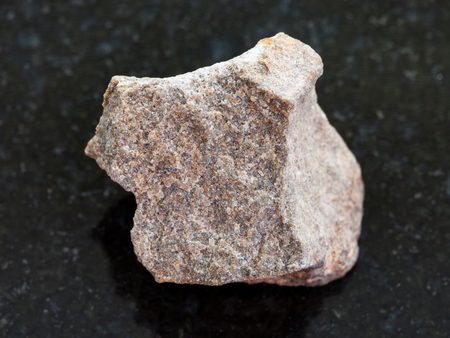 天然鉱物岩石標本のマクロ撮影-暗い花崗岩の背景にラフ珪岩石