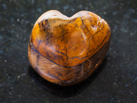 macro shooting of natural mineral rock specimen - polished tiger-eye stone on dark granite background Stock Photo