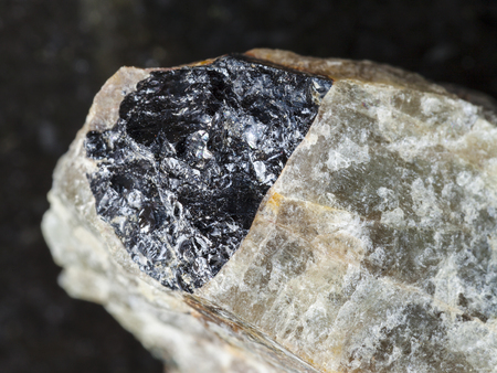 macro shooting of natural mineral rock specimen - black Ilmenite in rough green Nepheline stone on dark granite background from Krasnoyarsk Krai, Russia