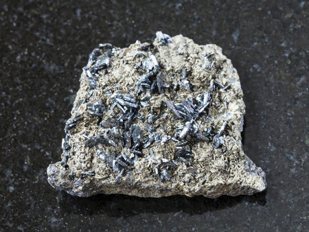 magnetite: macro shooting of natural mineral rock specimen - magnetite crystals on raw stone on dark granite background from Korshunovskoe mine, Irkutsk region, Russia