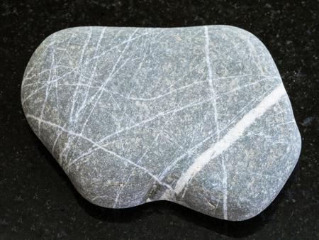 macro shooting of natural mineral rock specimen - pebble of Graywacke sandstone on dark granite background