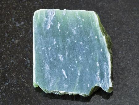 macro shooting of natural mineral rock specimen - raw nephrite stone slab on dark granite background