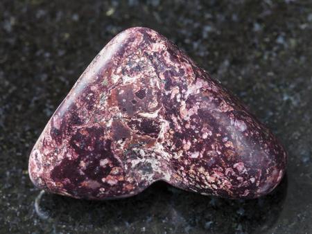 macro shooting of natural mineral rock specimen - polished Piemontite (manganese epidote) gemstone on dark granite background from Khalilovskoye mine in South Ural Mountains, Russia
